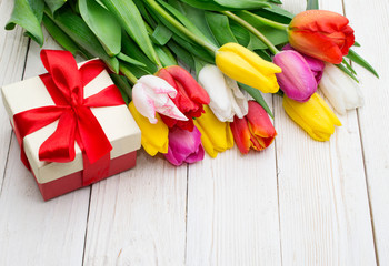 bouquet of tulips with a gift on rustic wooden board