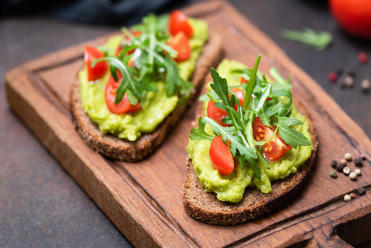 Healthy vegan toast with avocado, tomato, arugula on wooden serving board, closeup view, horizontal image. Snack, lunch or vegan breakfast
