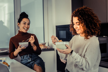 Curly red-haired woman enjoying her breakfast with friend