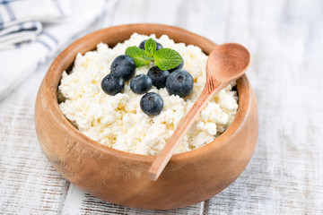 Closeup view of Cottage Cheese or Tvorog in wooden bowl on white wooden background. Closeup view. Cottage cheese with blueberries