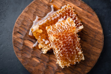 Honeycombs on wooden serving board. Top view selective focus