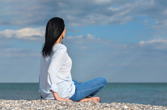 Caucasian  black hair  middle age woman looking at sea against  sky A single woman relaxing on beach  thinking about future.Summer holiday and vacation