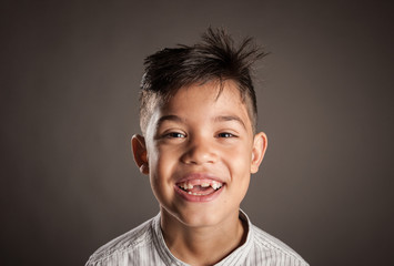portrait of happy kid smiling on a grey background
