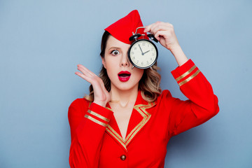 vintage stewardess wearing in red uniform with alarm clock