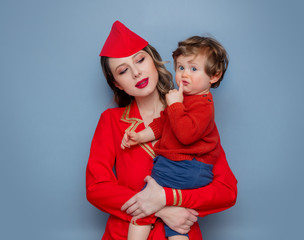 stewardess wearing in red uniform with a child on hands