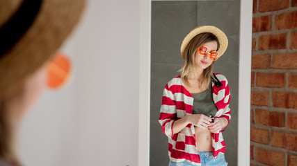 Happy yound woman dressing up near mirror in hat