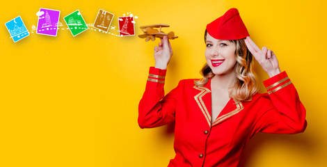 stewardess wearing in red uniform with wooden airplane.