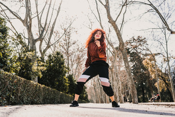 .Young and attractive latin woman dancing urban style on the street on a sunny winter day. Wear sports clothes Positive attitude, transmit happiness. Lifestyle.