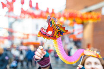 Girl holding chinese dragon at new year celebrations, London