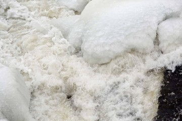 Ice cold water splashes from flowing river