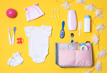 Flat lay composition with baby accessories and maternity bag on color background