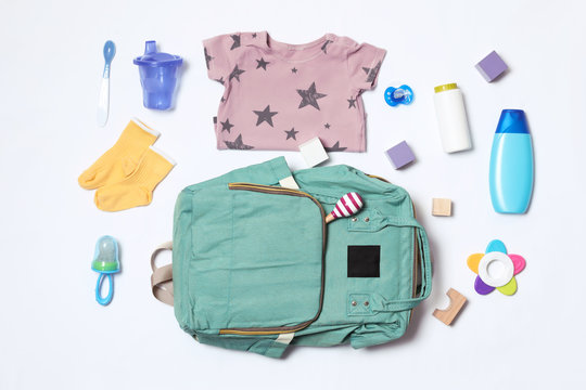Composition with maternity backpack and baby accessories on white background, top view