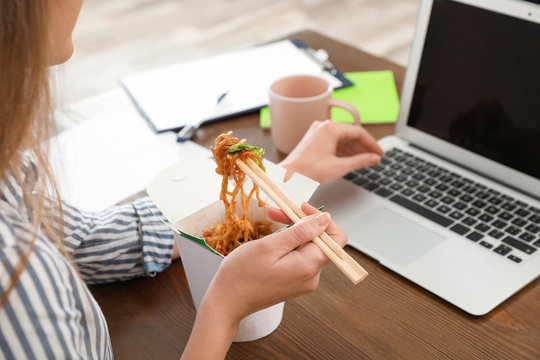 Office employee using laptop while having noodles for lunch at workplace, closeup. Food delivery
