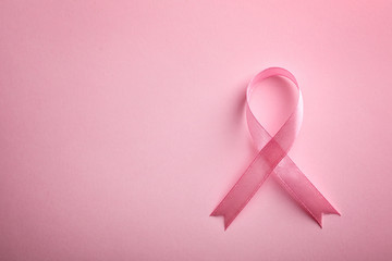 Pink ribbon on color background, top view with space for text. Breast cancer awareness concept