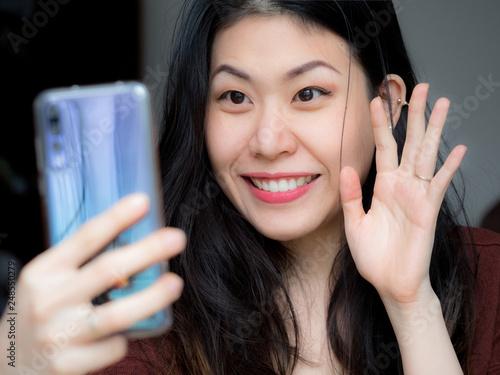 Asian young beautiful cheerful woman smiling, waving and