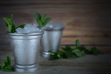 Image for Kentucky Derby in May showing two silver mint julep cups with crushed ice and fresh mint in a rustic setting. Vignette added. Copy space