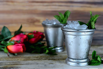 Image for Kentucky Derby in May showing two silver mint julep cups with crushed ice and fresh mint in a rustic setting with red roses
