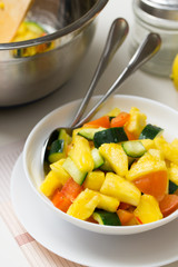 Fruit salad with pineapple, cucumber and tomato in bowl