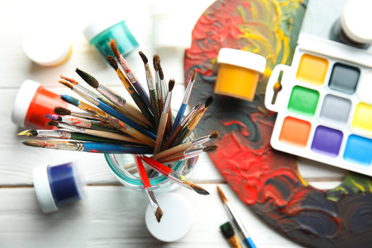 Glass jar with brushes, paints and palette on wooden background, top view