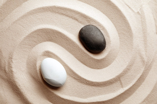 Zen garden stones on sand with pattern, top view. Meditation and harmony