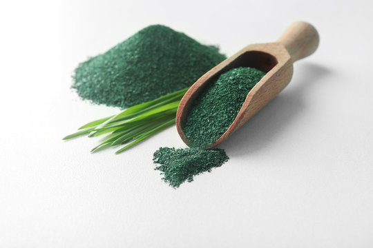 Composition with spirulina algae powder and grass isolated on white
