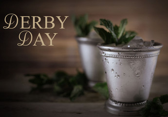 Image for Kentucky Derby in May showing two silver mint julep cups with crushed ice and fresh mint...