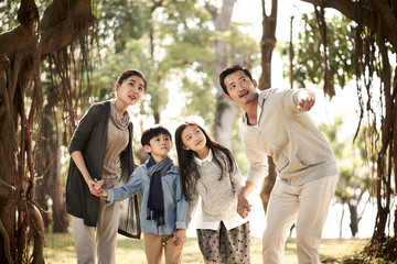 asian family with two children having fun in park