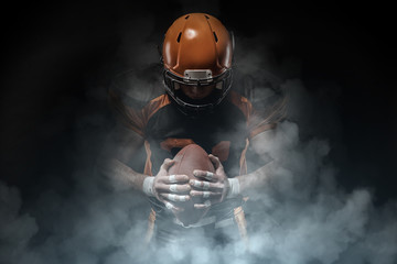 American football player on a dark background in smoke in black and orange equipment. Wall mural