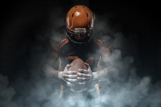 American football player on a dark background in smoke in black and orange equipment.