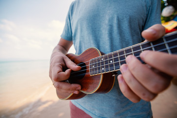 male hands closeup, man playing ukulele on tropical beach, music, art, travel and vacation concept