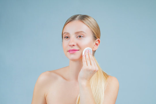 Beautiful woman removing makeup from her face