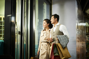 asian couple looking into shop window