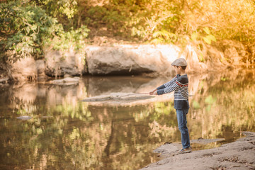Little Asian boy fishing at the river vintage  retro