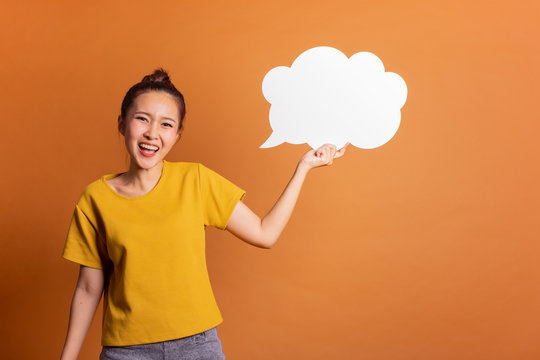 Young Asian woman show text box, speech bubble and copy space over orange background, empty space for text and ads, studio light