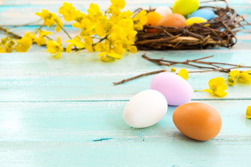 Wall Mural - Colorful Easter eggs in nest with flower on rustic wooden planks background. Holiday in spring season. vintage pastel color tone. Close up composition.
