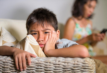 young sad and bored Asian child at home couch feeling frustrated and unattended while mother networking on mobile phone as internet addict neglecting her son Wall mural