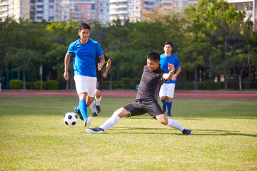 asian soccer players playing on field