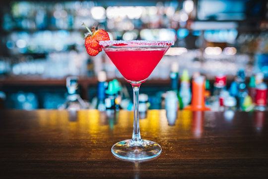 Red Strawberry Martini alcoholic drink cocktail on the bar table