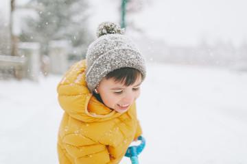 A happy little boy shovelling snow in winter.