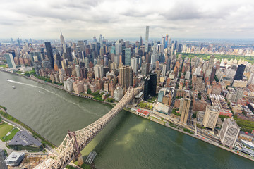 Wide-angle aerial view over the Ed Koch Queensboro Bridge and Midtown Manhattan, looking west
