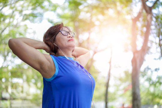 Senior asian woman relaxed listening to music in the park, Exercise sport activity concept