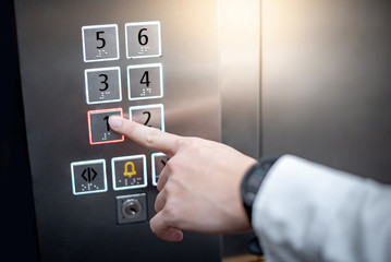 Male forefinger (index finger) pressing on the first floor button or floor number one in elevator (lift). Mechanical engineering concept
