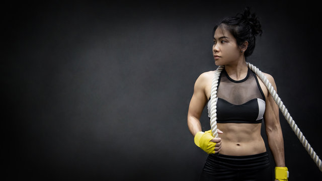 Asian girl fitness trainer posing with battle rope on shoulders on black background in studio. Physical exercise or workout in the gym. Muscular build or bodybuilding concepts