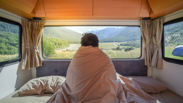 Young Asian man traveler staying in the blanket looking at mountain scenery through the window in camper van in the morning. Road trip in summer of South Island, New Zealand.