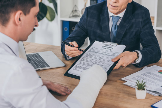 businessman in blue jacket giving form for compensation claim to worker with broken arm at table in office, compensation concept