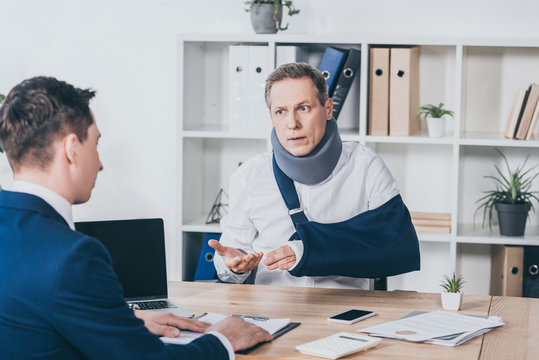 middle aged worker in neck brace with broken arm sitting at table and talking to businessman in blue jacket in office, compensation concept