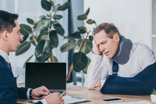 upset worker in neck brace with broken arm sitting at table opposite businessman in blue jacket in office, compensation concept