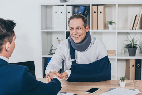 worker in neck brace with broken arm and businessman in blue jacket shaking hands over table in office, compensation concept