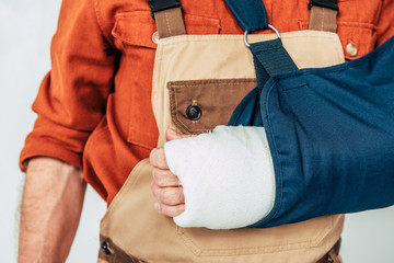 cropped view of repairman with broken arm and bandage on white background