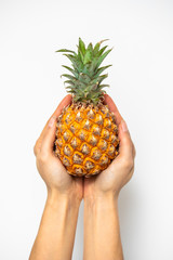 pineapple in hand close up on white background